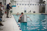 "Jack Killcoyne, a junior, pilots his team's boat in the Brooklyn Technical High School Cardboard Boat Regatta in the school's pool in Brooklyn in New York on Friday, March 1, 2013. As part of Engineering Week the teams of students constructed boats made only of cardboard and duct tape. The team's assigned ""captain"" piloted their boat from one end of the pool to the other and back in a heat with other boats, hopefully without sinking. The surviving boats were timed and the winners received bragging rights with an award also going to the most spectacular sinking. (© Richard B. Levine)"