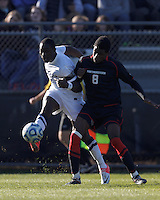 University of Connecticut forward Stephane Diop (5) crosses the ball as Northeastern University forward Terence Carter (8) defends..NCAA Tournament. University of Connecticut (white) defeated Northeastern University (black), 1-0, at Morrone Stadium at University of Connecticut on November 18, 2012.