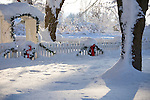 Idaho, Dalton Gardens. Coeur d' Alene. Wreaths with red bows, and Christmas garland decorate a white picket fence and arbor in a white snowy landscape while snow falls from the tree branches.