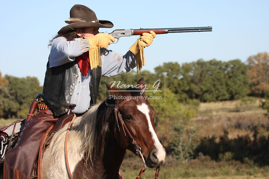 A cowboy taking aim with his rifle while on horseback