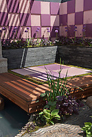 Outdoor meditation room with Japanese Oriental style design garden and deck surrounded by water garden, with raised beds of Allium and Heuchera, and checkerboard pattern purple and pink wall, for a color theme harmony and sense of enclosure and peace