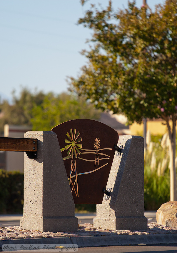 "Iron plates with windmill cutouts play a key part of the Grand Avenue Beautification Project.  This one is backlit by a setting sun illuminating trees.  This was part of the 2015 rebuild of the Grand Avenue and Diamond Bar Boulevard intersection for Diamond Bar's 2015 ""Grand Avenue Beautification"" project, landscape architecture for the project was by David Volz Design."