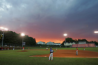 High school baseball game at sunset.