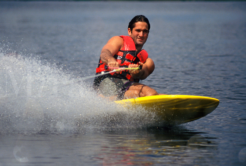 Male knee skiing on a lake with water spraying