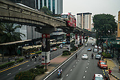 A monorail approaches while pedestrians cross the street in downtown Kuala Lumpur, Malaysia.