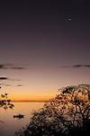 Rakiraki, Viti Levu, Fiji; a small boat is silhouette against an orange sunset sky reflecting in the bay in front of Volivoli Beach Resort, the northern most point of Viti Levu Island