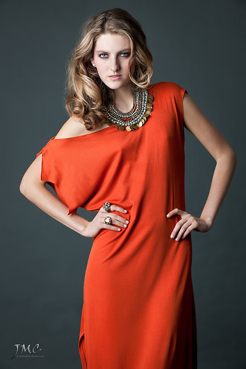 Beautiful young fashion model posing in orange dress, copper & pearl necklace