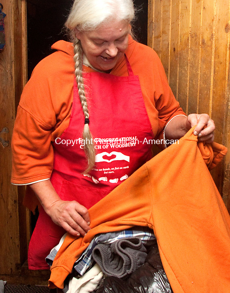 WOODBURY, CT 23 SEPTEMBER 2015 -093015DA01- Mary MacLead holds a stained unwearable shirt that will be added to others and transported to be recycled from the Red Barn Thrift Shop in Woodbury on Wednesday. The EPA and DEEP both estimate that only about 15 percent all discarded textiles, that includes clothing, curtains, blankets and ect. is recycled.<br /> Darlene Douty Republican-American