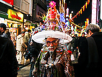 Senior citizen wearing a crazy man made hat constructed on a light shade that lights up,