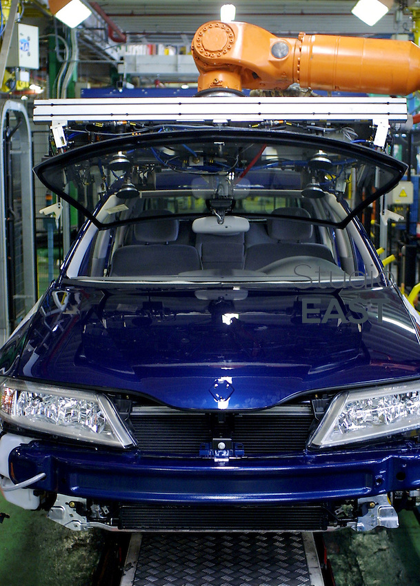A robot fixes the windshield of a Renault Laguna car, in Renault plant, in Sandouville, France, on September 18, 2002. Photo by Lucas Schifres/Pictobank