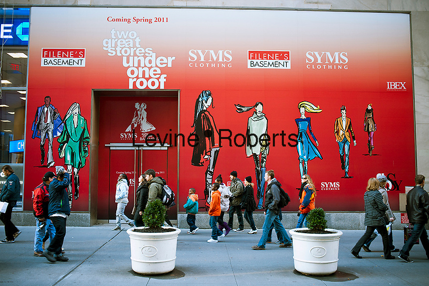 A construction shed on Fifth Avenue in New York on Thursday, November 23, 2001 promotes the future arrival of a Syms and Filene's Basement store which will probably not happen. Syms Corp. and its affiliate Filene's Basement are under bankruptcy protection and are liquidating all their stock as the businesses are shut down. The 25 existing Syms and the 21 exisiting Filene's Basement stores are set to close in January 2012.  (© Richard B. Levine)