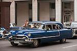 Havana, Cuba; a blue, classic 1956 Cadillac car, serving as a taxi, driving down the street in Havana