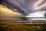 Beach walkers stop to look at a storm front passing over Shell Point Beach, Florida as they head home before the rain arrives.