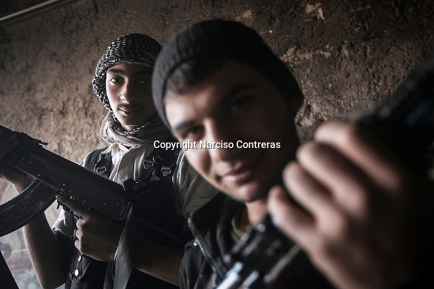 Mahmud (back) a seventeen years old, and Hassan (front) a sixteen years old fighters, pose for photo at Al Amiriyah neighborhood, a battlefield southwest of Aleppo, Syria.