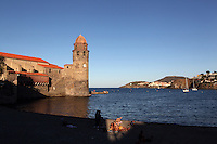 Tourists on Boramar Beach with the  Eglise Notre Dame des Anges in the background, Collioure, France. The bell tower was converted from a medieval lighthouse and the Mediterranean Gothic style nave was built in 1684. The dome was added to the bell tower in 1810. Picasso, Matisse, Derain, Dufy, Chagall, Marquet, and many others immortalized the small Catalan harbour in their works. Picture by Manuel Cohen.