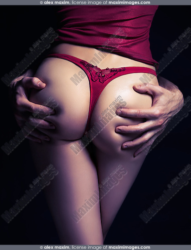 Artistic erotic concept of man hands on buttocks of a sexy young woman in red underwear isolated on black background