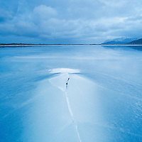 Crack in ice on frozen coastline at Ytterpollen, Lofoten Islands, Norway