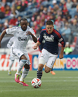 New England Revolution midfielder Kelyn Rowe (11) brings the ball forward as Vancouver Whitecaps FC midfielder Nigel Reo-Coker (20) closes. In a Major League Soccer (MLS) match, the New England Revolution (blue/white) tied Vancouver Whitecaps FC (white), 0-0, at Gillette Stadium on March 22, 2014.
