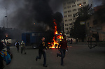 Protesters run past burning police carriers on Ramsis Street, Cairo, Egypt, Friday, Jan. 28, 2011. Tens of thousands of people took to the streets after Friday prayers, demanding that President Hosni Mubarak step down. Demonstrators clashed with police throughout the day and night as they marched toward Tahrir Square.