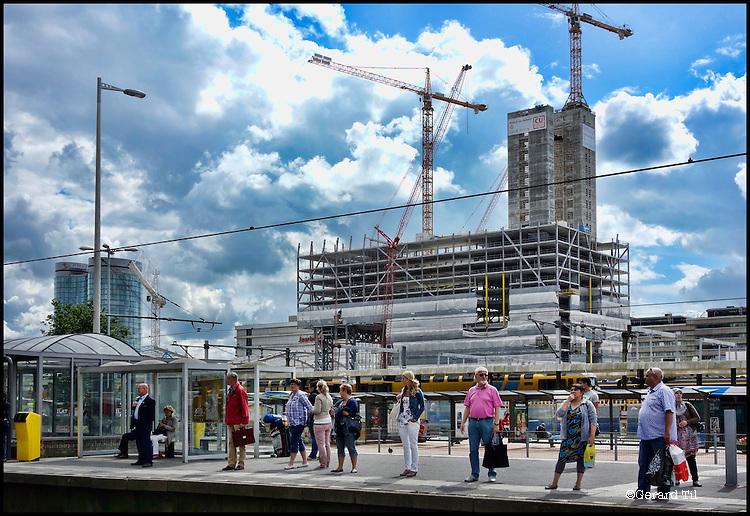 Nederland, Utrecht, 30-07-2012 Nieuwbouw stadskantoor. Stadskantoor Utrecht omvat 66.000 m2 en is een van de grootste gebouwen die vanaf medio 2011 wordt gebouwd in Nederland. Het stadskantoor wordt voor de Utrechter het centrale punt waar men terecht kan voor bijna alle gemeentelijke diensten en producten. Met een maximale hoogte van 92 meter is het straks het hoogste en een van de grootste stadskantoren van Nederland. Het project wordt gerealiseerd door Bouwcombinatie SKU, een samenwerking tussen VolkerWessels ondernemingen Boele & van Eesteren en G&S Bouw. De mesne op de voorgrond staan bij een sneltram halte. FOTO: Gerard Til / Hollandse Hoogte