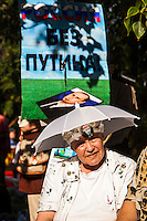 Moscow, Russia, 19/08/2012..A demonstrator in front of a poster reading ?Russia Without Putin? at an opposition rally. Several hundred opposition demonstrators gathered near the Russian government White House to mark the 21st anniversary of the attempted coup in 1991 by Communist hardliners that led to the eventual break-up of the Soviet Union.