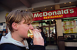 Europe, Great Britain, Birmingham. Youth eats burger outside Macdonalds fast-food restaurant. 2001.'MEAT' across the World..foto © Nigel Dickinson