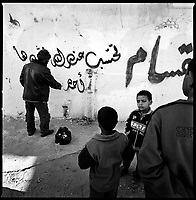 Rafah, Gaza Strip, Jan 15 2009.A spublic painter writes the name of Sheghda el Kurd on his family home wall; he was a prominent local Hamas fighter who was among the 7 men killed overnight in Israeli bombing and shelling, including 4 in the destruction of Abrahr mosque, the largest in Rafah.