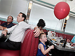 Manchester, New Hampshire: June 8, 2011<br /> Presidential candidate Rick Santorum (at left) campaigns inside the Airport Diner. Behind him a boy plays with a balloon. &copy;Chris Fitzgerald / Candidate Photos