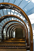 """The wonderfully designed semi-circular staircase at the Rookery Building, a historic landmark located in the Loop community area of Chicago in Cook County, Illinois, United States. Completed by John Wellborn Root and Daniel Burnham of Burnham and Root in 1888, it is considered one of their masterpiece buildings. It once housed the office of the famous architects. It measures 181 feet (55 m), is twelve stories tall and is considered the oldest standing high-rise in Chicago. It has a unique style with exterior load-bearing walls and an interior steel frame. The lobby was remodeled in 1905 by Frank Lloyd Wright. Starting in 1989, the lobby was again restored to the original Wright design..The Rookery was built in 1887-1888 in the architectural boom that followed the Great Chicago Fire, architects in what would become known as the Chicago School of commercial architecture competed with each other to create the world's first true skyscrapers. By mixing modern building techniques, such as metal framing, fireproofing, elevators and plate glass, together with traditional ones, such as brick facades and elaborate ornamentation, Burnham and Root sought to create a bold architectural statement. At the same time, they intended their buildings to be commercially successful. This building is one of the few results of their partnership that is still standing.. As the master artisan, Root drew upon a variety of influences in designing the interior and exterior spaces, including Moorish, Byzantine, Venetian and Romanesque motifs. He also provided the architectural innovations that brought together many contemporary cutting edge building techniques. Of particular note was a """"floating"""" foundation--a reinforced concrete slab that provided the building's weight with a solid platform atop Chicago's notoriously swampy soil. The term for the type of foundation that Root designed is grillage foundation, a foundation where iron rails and the structural beams are combined in a crisscross patt"""