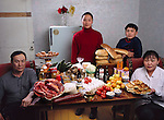 (MODEL RELEASED IMAGE). The Batsuuri family in their single-room home (a sublet in a bigger apartment) in Ulaanbaatar, Mongolia, with a week's worth of food. Standing behind Regzen Batsuuri, 44 (left), and Oyuntsetseg (Oyuna) Lhakamsuren, 38, are their children, Khorloo, 17, and Batbileg, 13. The Batsuuri family is one of the thirty families featured in the book Hungry Planet: What the World Eats (p. 226).