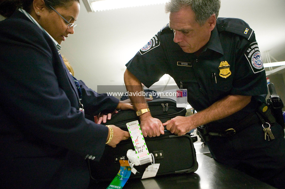 11 April 2006 - New York City, NY - CBP officer Robert Sotero (R) and tries to close an item of luggage not collected by passengers, known as LOBs for leftover bags, with help from an unidentified airline employee at JFK airport in the Queens borough of New York City, USA, 11 April 2006.