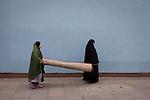 Muslim women carry heavy carpet along street on Walworth Road, Elephant & Castle, London borough of Southwark.