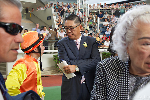 Owner of the legendary horse California Memory, Howard Liang, talks with jockey Matthew Chadwick at the Hong Kong Jockey Club's Shatin Racecourse. Trainer Tony Cruz is on the left.