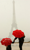 The Eiffel Tower with bright umbrelled visitors during a sudden hail storm - Photograph by Owen Franken