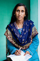 Jesmin Akhter, 26 (in turquoise & blue), poses for a portrait in one of her 'marketplaces', Jerai Villlage, Gobindagonj Upazila, Gaibandha, Bangladesh on 19th September 2011. She has found financial independence and contributes to her household income by working as a saleswoman, earning 3500 - 5000 Bangladeshi Taka per month. She is the top saleswoman under her 'hub', out of 30 women. Having worked for about 2.5 years, she cycles from village to village and door to door in a country where women on bicycles is an extremely uncommon sight. She is one of many rural Bangladeshi women trained by NGO CARE Bangladesh as part of their project on empowering women in this traditionally patriarchal society. Named 'Aparajitas', which means 'women who never accept defeat', these women are trained to sell products in their villages and others around them from door-to-door, bringing global products from brands such as BATA, Unilever and GDFL to the most remote of villages, and bringing social and financial empowerment to themselves.  Photo by Suzanne Lee for The Guardian