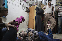 June 09, 2015 - Beirut, Lebanon: Widaad (centre)) stands beside her husband Jamal (right) as Jamal's brother, who suffers from a disability, lays on the ground at their room house in Shatila refugee camp. They are Syrian refugees from the city of Al Qusayr from where they fled four years ago when the fighting sparked out between opposition armed groups against loyalists to President Bashar Al-Assad. (Photo/Narciso Contreras)
