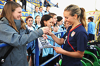 USA defender Heather Mitts signs an autograph for a fan.  The USA was victorious over Sweden 2-0 in Ferreiras on March 1, 2010 at the Algarve Cup.