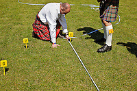 A putting ball throw is measured in a competition at the Helensburgh and Lomond Highland Games in Argyll.
