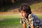 Happy smiling boy in the park near to sunset with shallow depth of field and copy space to left