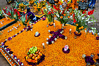 A Mexican woman sits at the flower-decorated gravesite to honor her deceased relatives during the Day of the Dead celebration in Tzintzuntzan, Michoacán, Mexico, 2 November 2014. Day of the Dead ('Día de Muertos') is a syncretic religious holiday, celebrated throughout Mexico, combining the death veneration rituals of the ancient Aztec culture with the Catholic practice. Based on the belief that the souls of the departed may come back to this world on that day, people gather on the gravesites praying, drinking and playing music, to joyfully remember friends or family members who have died and to support their souls on the spiritual journey.