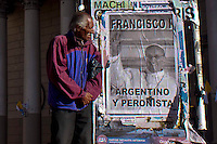 "A man walks next to a poster of Pope Francis than reads in spanish ""Argentinean and Peronist"" in a street in Buenos Aires March 17, 2013. Photo by Juan Gabriel Lopera / VIEWpress."
