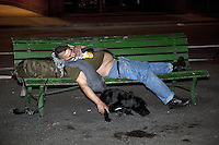 Switzerland. Geneva. Paquis neighborhood, known for its nightlife. A man is sleeping on a green bench. He is fully drunk. His black dog in lying on the ground. 24.03.12 &copy; 2012 Didier Ruef