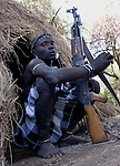 Young man with gun AK47, Mursi Tribe, Mago National Park, Lower Omo Valley, Ethiopia, portrait, person, one, tribes, tribal, indigenous, peoples, Southern, ethnic, rural, local, traditional, culture, primitive, Rifle, Weapon, Assault, hut, Kalashnikov.Africa....