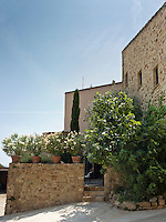 An exterior view of the house with a walled courtyard lined with potted oleander plants