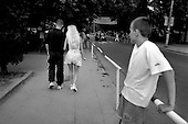 """Jastrzebia Gora, Poland.August 1997.The """"look"""".  A young Polish couple stroll down the street of a Baltic beach town in the style know as """"DRESS"""". Crew cut, jogging pants for the man. Pump heals, short skirt, long legs and blond hair for the woman. A young boy takes it all in.."""