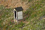 White wooden outhouse on a hillside at a Colorado mining camp