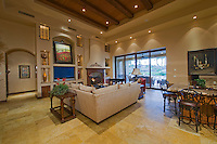 Beige sectional sofa is seen in Mediterranean decore family room with tall beamed ceilings