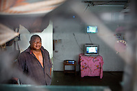 """Darnard, a security agent and weightlifter, back home after work. Security companies are one of the main employer on the island, along with the government...Scene at the """"Locations"""", a poor area where foreign workers from other Pacific islands (Tuvalu, Kiribati, Fidji etc) were housed, after they came to work in the Phosphate mining industry...Nauru, officially the Republic of Nauru is an island nation in Micronesia in the South Pacific.  Nauru was declared independent in 1968 and it is the world's smallest independent republic, covering just 21square kilometers..Nauru is a phosphate rock island and its economy depends almost entirely on the phosphate deposits that originate from the droppings of sea birds. Following its exploitation it briefly boasted the highest per-capita income enjoyed by any sovereign state in the world during the late 1960s and early 1970s..In the 1990s, when the phosphate reserves were partly exhausted the government resorted to unusual measures. Nauru briefly became a tax haven and illegal money laundering centre. From 2001 to 2008, it accepted aid from the Australian government in exchange for housing a Nauru detention centre, with refugees from various countries including Afghanistan and Iraq..Most necessities are imported on the island..Nauru has parliamentary system of government. It had 17 changes of administration between 1989 and 2003. In December 2007, former weight lifting medallist Marcus Stephen became the President."""