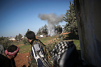 In this Saturday, Dec. 15, 2012 photo, Syrian rebel fighters react as a tank shell lands nearby them during heavy clashes inside one militar academy besieged by rebels at the north of Aleppo, Syria. The Free Syrian Army took control over the Academy after several hours battling the troops loyal to President Bashar al-Assad. Among the casualities are one FSA General and one Syrian journalist. (AP Photo/Narciso Contreras)