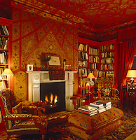 The ornately decorated red and gold walls of this library are covered in hand-painted wallpaper and the furniture  in rich tapestry and textiles